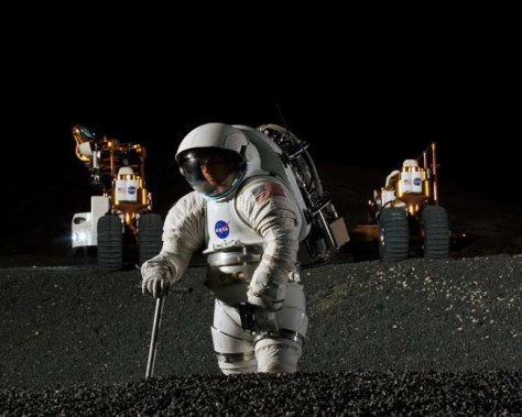 Image: Spacesuit engineer Dustin Gohmert simulates work in a crater of Johnson Space Center's Lunar Yard, while his ride, NASA's new lunar truck prototype, stands ready in the background.