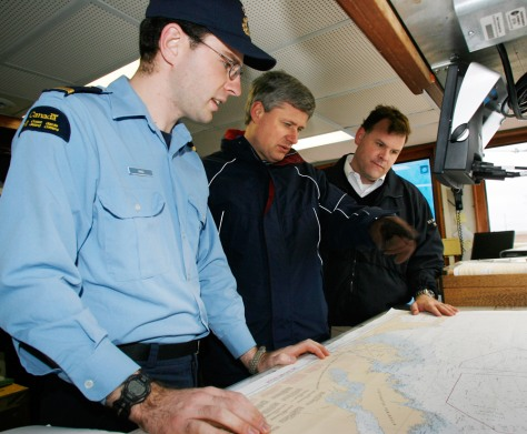 Image: Canadian Prime Minister Stephen Harper, center, and Minister of the Environment John Baird, right, with navigator Ryan Hull