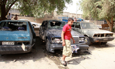 Image: Boy in front of damaged vehicles