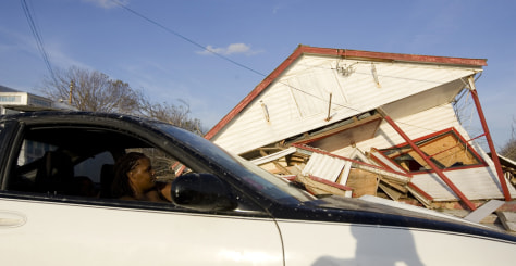 Image: A woman drives past a house destroyed by Hurricane Ike