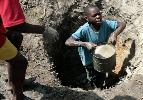 Image: A young boy lifts a bucket filled with ground water in Harare, Zimbabwe.