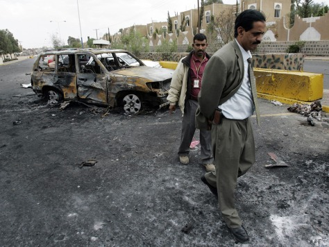 Image: Two U.S. Embassy employees inspect damaged vehicles in front of the site's main entrance in San'a, Yemen