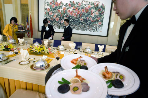 Image: Chinese waiters and waitresses prepare a lunch for a high-level official event