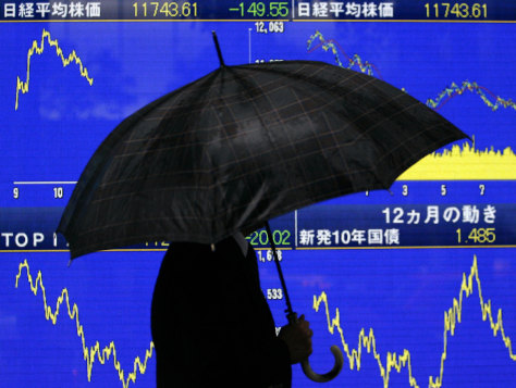 Image: A man carrying an umbrella strolls past a stock board outside a securities firm in Tokyo, Japan