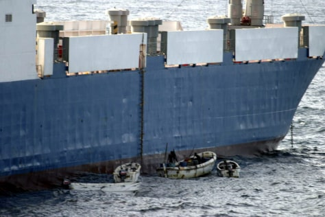 "Image: Somali pirates in small boats alongside hijacked ""Faina."""