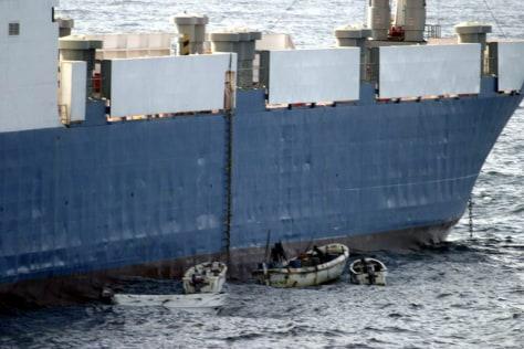 """Image: Somali pirates in small boats alongside hijacked """"Faina."""""""