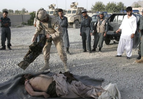 Image: A Canadian soldier looks at the body of a suspected Taliban