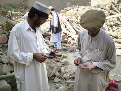 Tribesmen show parts of missile at site of missile attack in village of Tappi near Afghan border