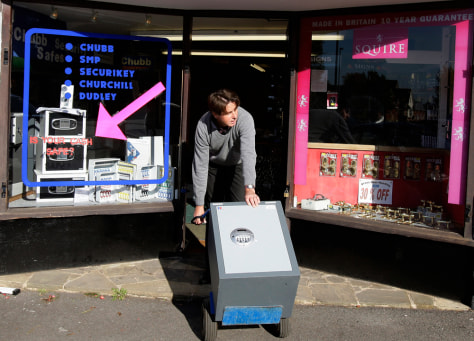 Image: A shop owner moves a safe