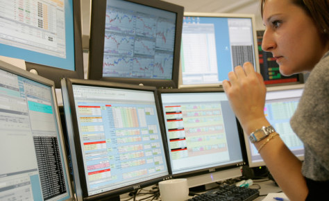 Image: A trader checks screens on London stock market