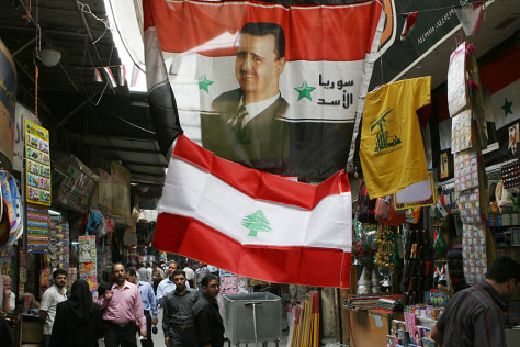 Image: A picture of Syrian President Bashar Assad is printed on a flag