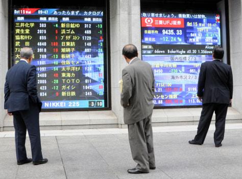 Image: Pedestrians study stock indicators in Tokyo