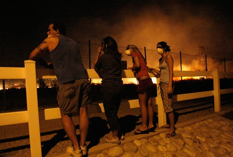 Image: Residents watch as a brush fire burns
