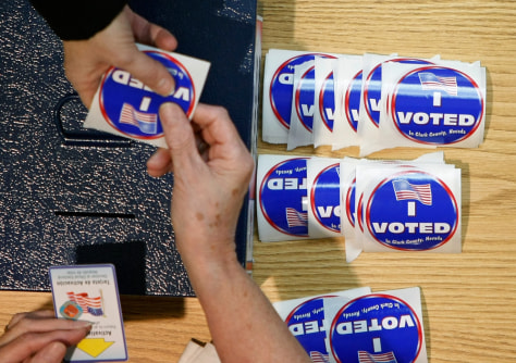 Image: An election worker hands out stickers