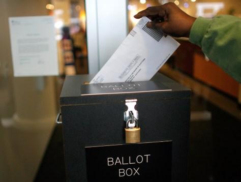Image: A voter drops off an absentee ballot