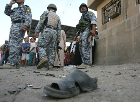 Image: Iraqi forces stand guard after a car bomb explosion in Baghdad.