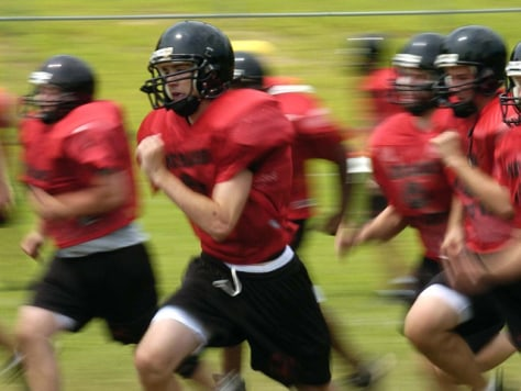 Image: Madison High School football players run sprints