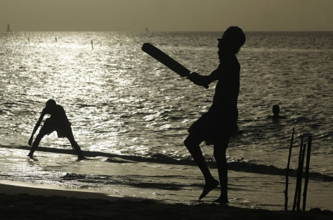 Image: Locals play cricket on the beach in Grenada
