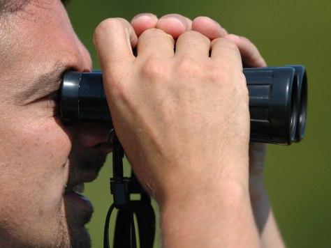 Image: Man looking through binoculars