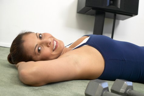 Portrait of a young woman doing sit-ups