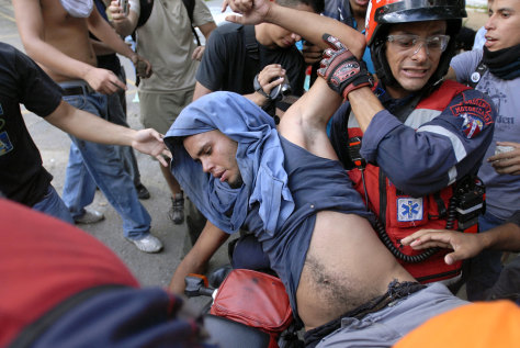 IMAGE: A paramedic carries an opponent of President Hugo Chavez.