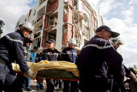 Image: Rescue personnel carry the body of a bomb blast victim near the Constitutional Court building in Algiers.