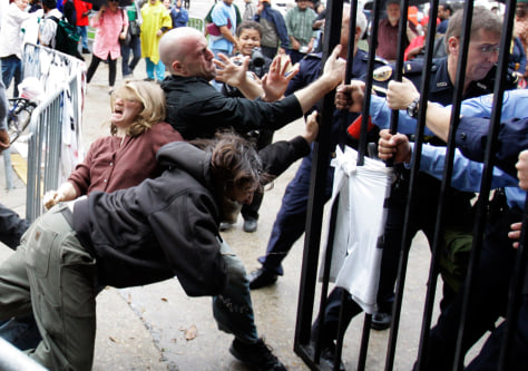 Image: Protesters fall to the ground as New Orleans Police re-lock a gate outside the New Orleans City Council chambers.