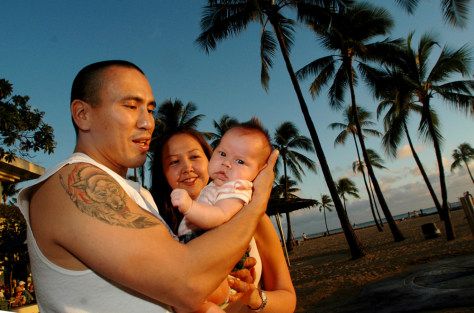Image: Alaskans Jeremy Esmailka and his wife Deanza Hjalseth stand with their baby Sienna, on Waikiki beach in Honolulu, Hawaii