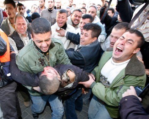 Image: People carry the body of a Palestinian after he was killed by Israeli troops during a raid in Gaza.