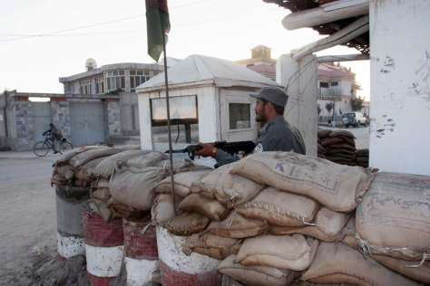 Image: An Afghan policeman keeps guard in front of the office of Asian Rural Life Development Foundation.