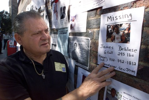 Image: James Deblase looks at a photo of his son posted on the wall outside the 69th Regiment Armory in New York after the Sept. 11 attacks.