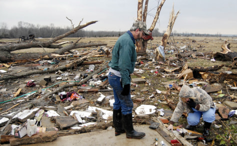 Image: Clay and Seavia Dixon pick through the debris of what is left of their tornado damaged home.