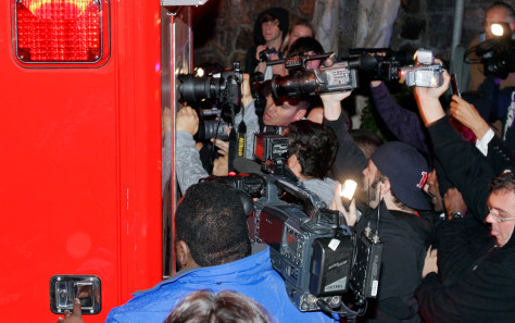 Image: Photographers try to get a shot of Britney in ambulance.