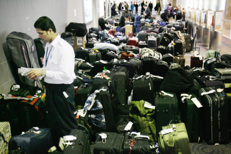 Image: Airport worker surrounded by backlogged luggage