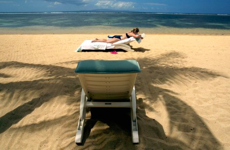 Image: A tourist sunbathes at Sanur Beach, Bali
