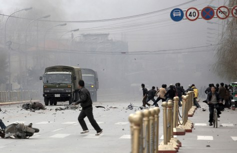 Image: Tibetans throw stones at army vehicles.
