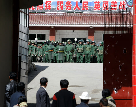 Image: Tibetans look at Chinese riot police in Xiahe, Gansu province