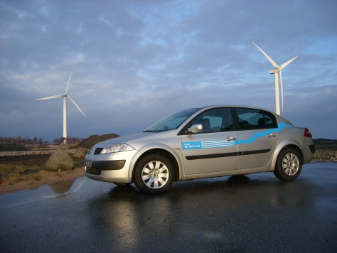 IMAGE: ELECTRIC CAR NEXT TO WIND TURBINES
