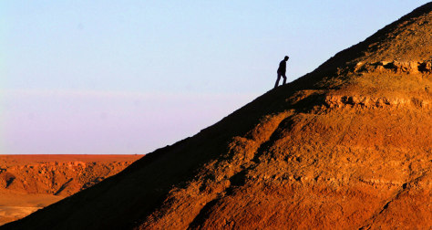 Image: A tourist climbs to the top of Ait Ben Haddou fortress near Ourzazate, Morocco