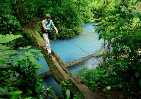 Image: A Spanish tourist crosses a bridge over the Celeste river at Tenorio Volcano National Park in Upala