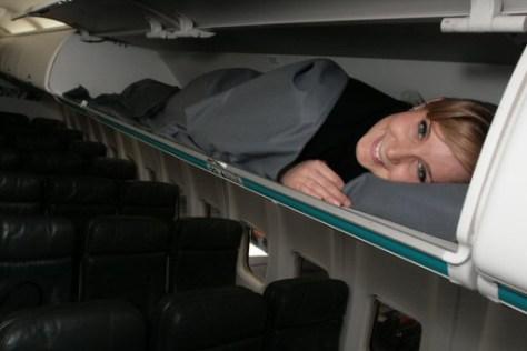 Image: WestJet guest lies in an overhead cabin