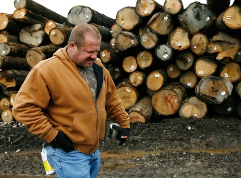 Image: Man walks by a stack of logs
