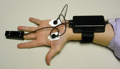 Image: Hand splayed out, with fingertip clamp and sensors on palms