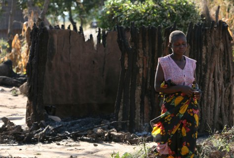 Image: Getrude Rengesai walks past her burnt hut at Mount Panis Farm in Centenary
