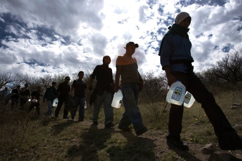 Image: Migrants carry water