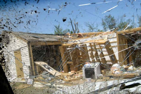 Image: A tornado damaged home is seen through a cracked windshield of a truck