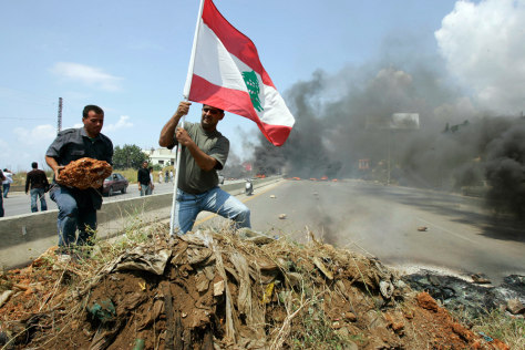 Image: Pro-government loyalists plant a Lebanese flag