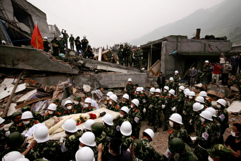 Image: Rescuers carry out a survivor