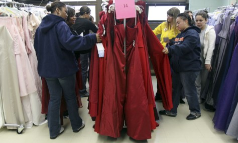 Image: Volunteers and students browse through racks of recycled prom dresses