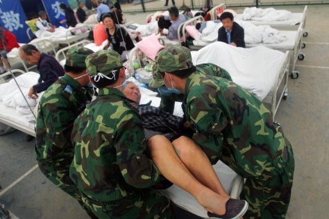 Image: Chinese soldiers lift an earthquake survivor